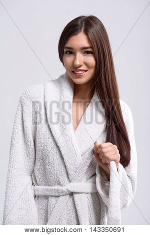 Joyful girl is standing and relaxing in white bathrobe. She is looking at camera with happiness and smiling. Isolated