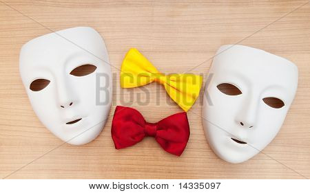 Masks and bow ties on the wooden background