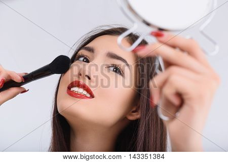 Cheerful girl is applying blush on face and smiling. She is holding brush and mirror. Lady is standing and smiling