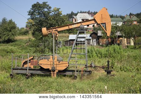 Pumpjack for oil production, set near the village