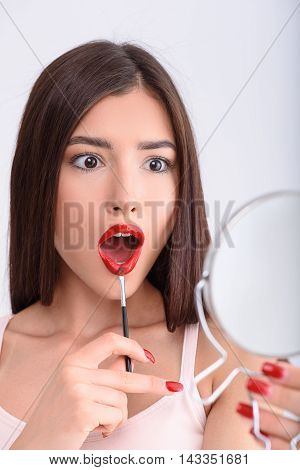 Attractive girl is doing facial make-up. She is standing and touching brush to lips. Lady is opening mouth and looking at mirror with surprise. Isolated