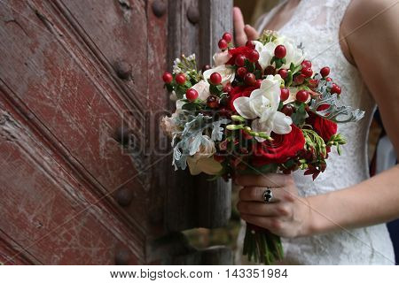 Beautiful wedding bouquet in hands of the bride against the background of vintage doors. Wedding vows.