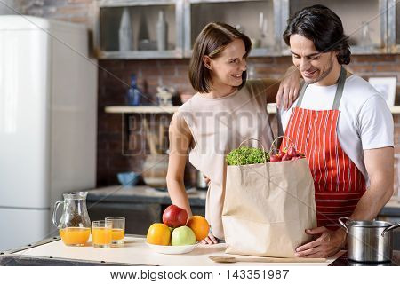 Lets cooking healthy food. Cheerful husband and wife are standing and embracing in kitchen. They are smiling. Man is holding packet of vegetables