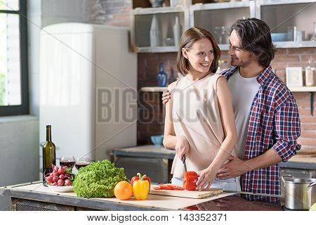 Happy married couple is cooking healthy food together. Woman is standing and cutting pepper. Woman is embracing her. They are smiling