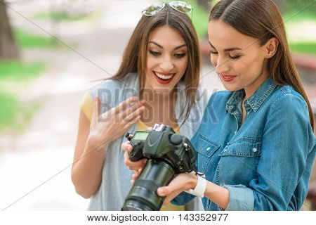Skillful female photographer is showing photos to young woman. They are looking at camera and smiling. Girls are standing in park