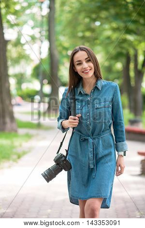 Joyful female photographer is walking in park. Woman is carrying camera and smiling