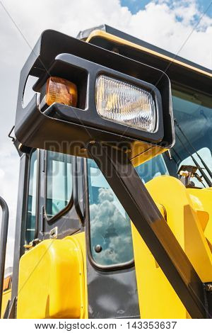 parking lamp on a yellow tractor. plastic two-tone parking lamp. focus on the parking lamp