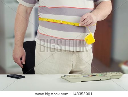 Standing over-weighted man measures his stomach with yellow tape meter around. He wears striped short sleeve t-shirt and light gray pants. His body is photographed only. There are gray keyboard, mobile phone on white desk