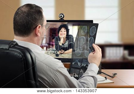Neurosurgeon attentively looks at patients brain x-ray results. Doctor sits at the desk opposite monitor with web-cam where middle-aged cheerful woman measures her blood pressure