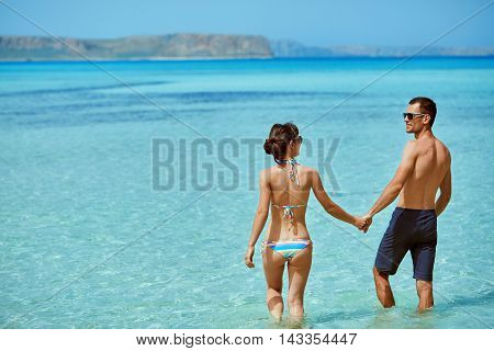 young happy couple in love walking on the beach at the sunny day. Balos beach, Crete, Greece. newlyweds in a honeymoon on the sea and islands