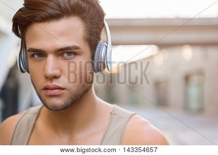 Attractive young man is listening to music from earphones. He is standing outdoors and looking forward with seriousness