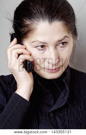 Beautiful mature asian woman talking on a cell phone on a gray background.