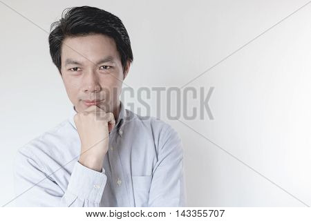 Young Asian man thinking on white background
