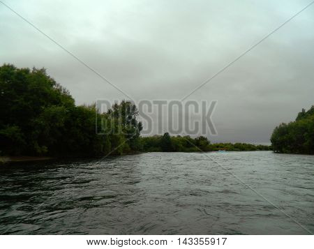 Beautiful landscape view of green forest and mountain background with flowing rafts river under cloudy sky on Kamchatka