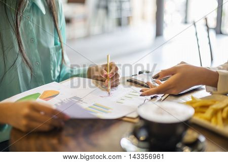 image of young women discussing a project in coffee shop