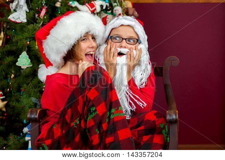 Silly siblings play Santa Claus. One has a beard and hat while her older sister sits on her lap. Both look happy and surprised.