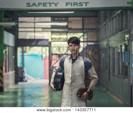 Industrial welder worker at factory workshop background
