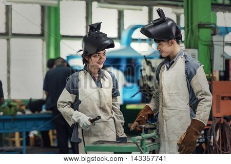 Industrial welder man and woman worker at factory