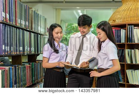 Portrait of students studying in library looking at the viewer with a cheerful