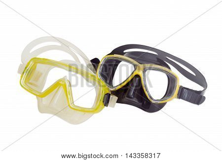 Two different diving masks - black and yellow and white and yellow on a light background