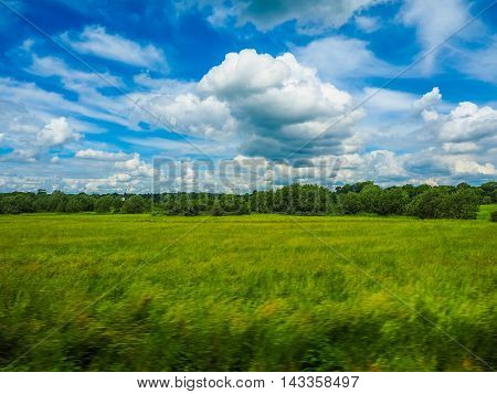 High dynamic range (HDR) English countryside seen from a train to London with selective focus on the horizon and motion blur on the foreground