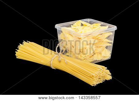 Uncooked bow-tie pasta in transparent plastic tray and bundle of dried long pasta on a dark background