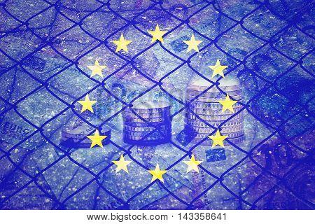 EU flag, euros, cracks and fence - Finance concept