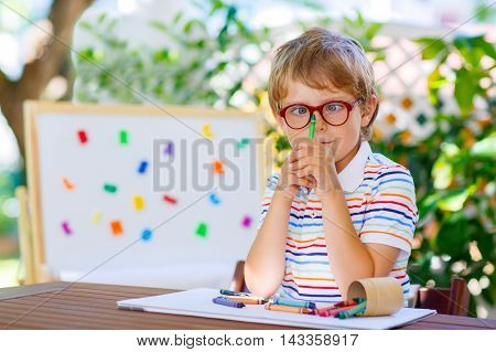 Funny adorable little kid boy with glasses holding wax crayons pens. Child and student is back to school and looking at pupil's stuff on warm day.