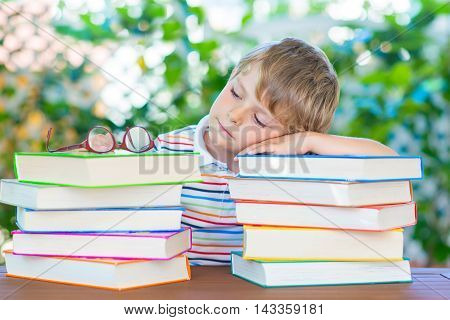 Frustrated and sad little kid boy with glasses and lots of colorful books. Child and student is back to school and is tired and disappointed on warm day.