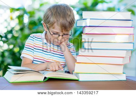 Adorable little kid boy with glasses and stack of colorful books. Cute child and student is back to school and reading on warm day.