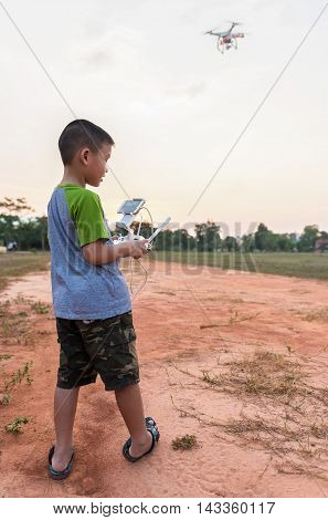 Portrait of kid with quadcopter drone outdoors. Happy boy playing with flying drone with camera controlled by smartphone