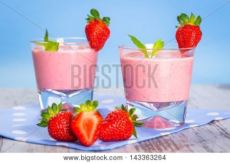 Glasses of strawberry smoothie on wooden table