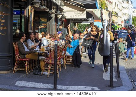 PARIS, FRANCE - MAY 12, 2015: Residents relax in one of the many cafes in the Montmartre district.
