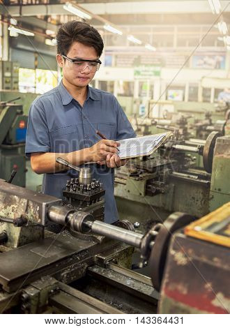Factory worker writing report quality control check