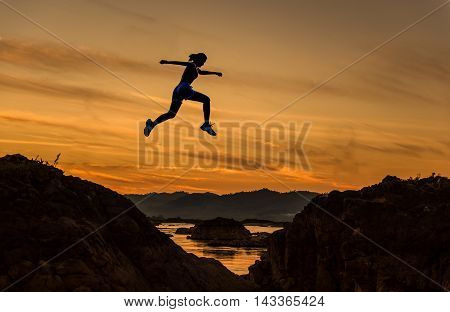 Woman jump through the gap between hill.man jumping over cliff on sunset backgroundBusiness concept idea