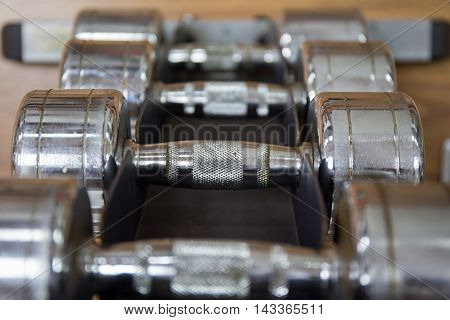close up group of dumbbells for weight training on rack in workout room