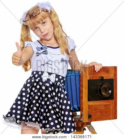 Cute little blond girl wearing glasses and fancy polka-dot dress, near a large, wooden, vintage camera-Isolated on white background