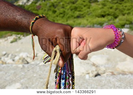 Hands of different races adorned with African bracelets making fist to fist agreement