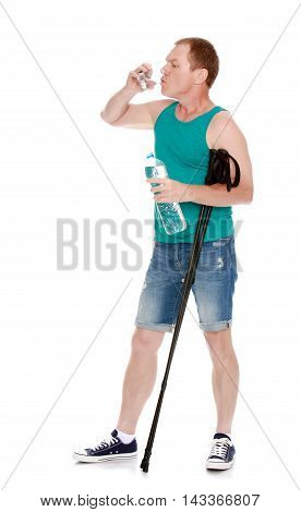 Man in t-shirt and shorts, with sticks for Nordic walking, drinking water from a glass -Isolated on white background
