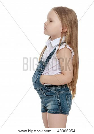 Offended little chubby girl with long blonde hair below the waist, short denim overalls. The girl turned away from the camera and turned sideways. Close-up