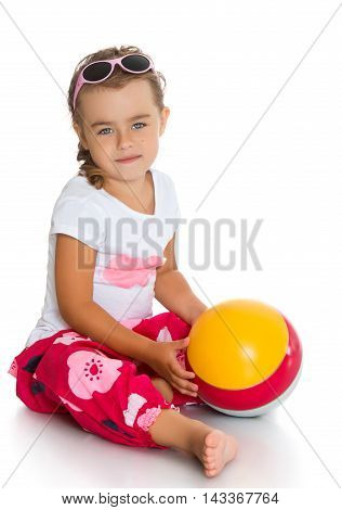 Beautiful little girl in glasses with the ball in his hands sitting on the floor-Isolated on white background