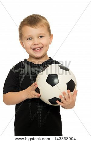 Portrait of a cheerful little boy football player in black uniform. The boy holds a hand soccer ball.Close-up - Isolated on white background
