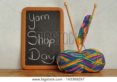 A blackboard with he words Yarn Shop Day and a ball of wool and knitting needles