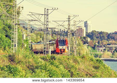 Modern high-speed train moves along Black sea coast. Sochi. Russia.