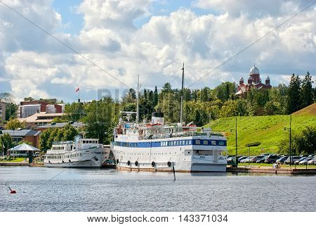 LAPPEENRANTA, FINLAND - AUGUST 8, 2016: Sumeer landscape with white boats on Saimaa Lake. On the right side is City Lutheran Church.