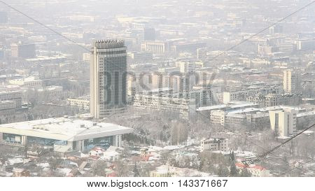 ALMATY, KAZAKHSTAN - MARCH 10 2014: view of the foggy city of Almaty and the Kazakhstan hotel - the famous landmark all over Almaty and serves as a symbol of the city.