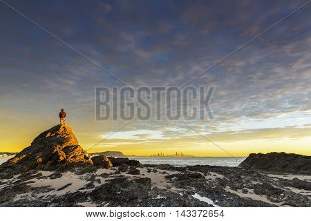Unidentified man standing on the top of a rock during sunrise at Currumbin Rock, Gold Coast.