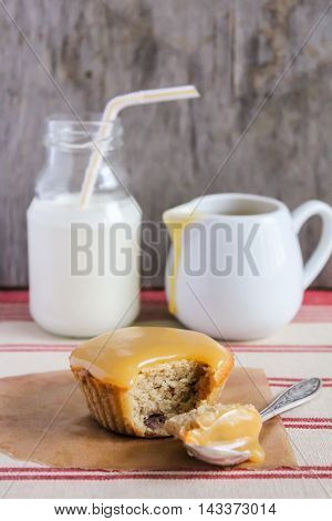 Sticky date pudding topped with caramel sauce served with fresh milk, selective focus