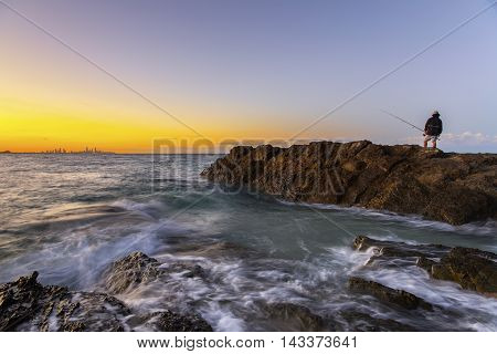 Fisherman fishing on the rock during clear sky sunset at Currumbin Rock, Gold Coast
