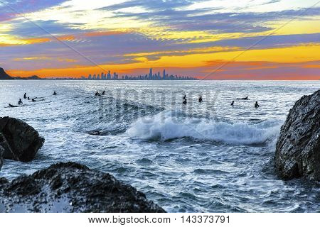 Colourful sunset with surfers sitting on their boards in the surf at Currumbin Rock Gold Coast